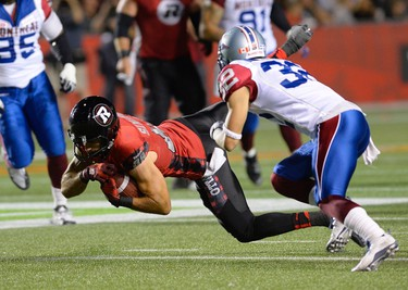 Ottawa Redblacks James Green (38) falls after being tackled by Montreal Alouettes Mitchell White (32) during the second half of a CFL game in Ottawa on Friday, Aug. 7, 2015. The Redbacks won 26-23. THE CANADIAN PRESS/Justin Tang