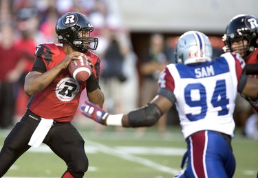 Ottawa Redblacks' quarterback Henry Burris (L) throws under pressure from Montreal Alouettes' Michael Sam (R) during the first half of their CFL football game in Ottawa, August 7, 2015. REUTERS/Christinne Muschi