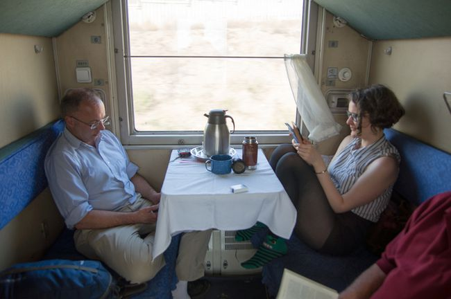 This April 30, 2015 photo shows Jeremy Hainsworth, left, and Shelagh Travers aboard the Trans Mongolian Express as it crosses Mongolia's Gobi Desert. The ride is the first leg of the Trans Siberian Railway trip covering 7,900 kilometers from Bejing, China to St. Petersburg, Russia. (Alexander Richard Whibley via AP)