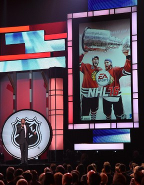 Host Rob Riggle unveils the cover of the EA Sports NHL 16 video game featuring Jonathan Toews and Patrick Kane from the Chicago Blackhawks during the 2015 NHL Awards at MGM Grand Garden Arena on June 24, 2015. (Ethan Miller/Getty Images/AFP)