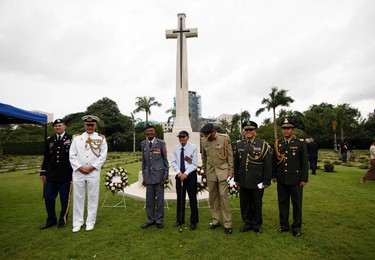 Diplomats and World War II veterans pose for photos during a ceremony to mark the 70th anniversary of the end of  World War II in the east, Saturday, Aug 15, 2014, at Hanthawaddy War Cemetery in Yangon, Myanmar. A group of World War II veterans from Myanmar's ethnic Karen minority, most in their 90s, prayed and sang a poignant hymn Saturday at the graveside of a legendary British officer who sacrificed his life for an ethnic group for whom the war's end 70 years ago led to the world's longest-running insurgency. (AP Photo/Khin Maung Win)