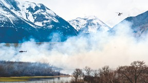 In this file photo Parks Canada helicopters fly over a controlled burn in late April 2015. Currently, Canadian firefighters are taking on a blaze south of the border in Montana. Greg Cowan photo/Pincher Creek Echo.