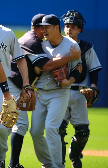 Yankee's pitcher Masahiro Tanaka celebrates his complete game victory  with a hug from Alex Rodriguez as Toronto Blue Jays lost 4-1 to the New York Yankees in Toronto, Ont. on Monday August 10, 2015. Michael Peake/Toronto Sun/Postmedia Network