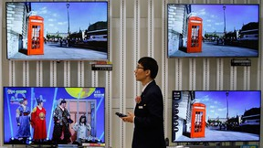 An employee uses his mobile phone in front of LG Electronics' organic light-emitting diode (OLED) TV sets, which are made with LG Display flat screens, at its store in Seoul Jan. 28, 2015. REUTERS/Kim Hong-Ji