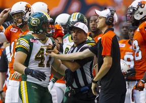Eskimos linebacker JC Sherritt is pushed back by a member of the B.C. Lions coaching staff and a referee earlier this month in Vancouver (Ben Nelms, Reuters).