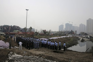 Representatives from the police and People's Liberation Army (PLA), marking the seventh day since the Tianjin explosions, pay tribute to the people who died, in a ceremony at Binhai new district, Tianjin, China, August 18, 2015. (REUTERS/Stringer)