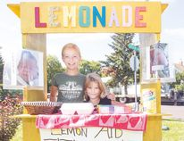 12-year-old Kara Anderson, left, and Sadie Chiponski, 8, ran a lemonade stand at Dickens Avenue over the weekend to help raise money for the Finnimore family who's newborn Joy was born with Cystic Hygroma. The family has moved to Winnipeg where their daughter will be treated at the Manitoba Children's Hospital. The young girls have a goal of raising $1,000 and have already surpassed $700. (Mickey Dumont/TheGraphic/Postmedia Network)