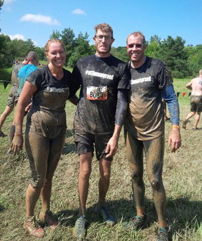 Tanya Dyke, left, and brothers Jonathan van Wyk and Brian van Wyk wear their mud-spattered #stthomasproud T-shirts at Tough Mudder competition last weekend north of Toronto.