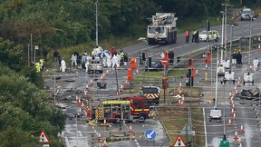 A crane arrives on site as emergency services and crash investigation officers continue to work at the site where a Hawker Hunter fighter jet crashed onto the A27 road at Shoreham near Brighton, Britain Aug. 24, 2015.  REUTERS/Luke MacGregor