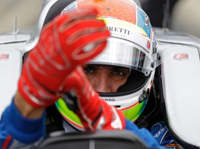 This is a May 14, 2015, file photo showing Justin Wilson, of England, putting on his gloves as he prepares to drive during practice for the Indianapolis 500 auto race at Indianapolis Motor Speedway in Indianapolis. The British driver was in a coma in critical condition after sustaining a head injury when he was hit by a large piece of debris that broke off another car in the crash-filled race at Pocono Raceway on Sunday, Aug. 23, 2015. (AP Photo/Michael Conroy, File)