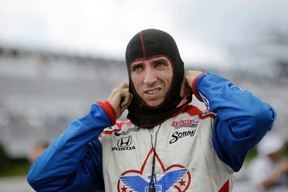 In this July 6, 2013, file photo, Justin Wilson, of England, pulls on his balaclava during a qualifying session for the Pocono IndyCar 400 in Long Pond, Pa. (AP Photo/Mel Evans, File)