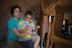 Leslie Lander and her autistic son Jordan in their Kanata home Monday afternoon. On Friday, Jordan ran from the backyard but was later found by an off-duty police officer who saved the boy from being hit by traffic. (DANI-ELLE DUBE/OTTAWA SUN)