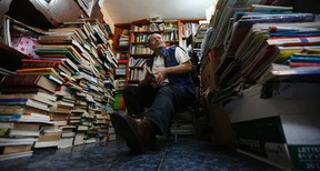 In this Aug. 19, 2015 photo, Jose Alberto Gutierrez sits among piles of books at his home in Bogota, Colombia. A second-grade education has not stopped garbage collector Jose Gutierrez from bringing the gift of reading to thousands of Colombian children. (AP Photo/Fernando Vergara)