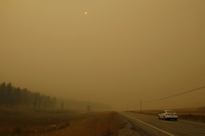 Thick smoke from nearby wildfires makes the sun an orange sphere high in the sky as seen from State Route 20 between Tonasket, Wash., and Republic, Wash., Wednesday, Aug. 26, 2015. (AP Photo/Ted S. Warren)