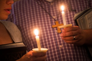 Community supporters light candles during a vigil for journalists Alison Parker and Adam Ward who were killed during a shooting in Moneta, Va., Wednesday, Aug. 26, 2015. Vester Lee Flanagan opened fire during a live on-air interview for WDBJ7, killing the two journalists Wednesday. (Autumn Parry/The News & Advance via AP)