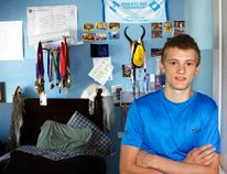 Canadian wrestling champion Connor McNeice stands in the doorway of his bedroom in front of about half of his wrestling medals that he has won as he is preparing to represent Canada at the World Wrestling Cadet Championships on Aug. 29 in Sarajevo.