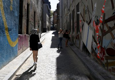 A tourist walks up a street covered with graffiti in the Marolles district in Brussels, Belgium, August 5, 2015. Once the last refuge of lepers and criminals, one of Brussels' quirkiest neighbourhoods teems with vintage furniture sellers, flea markets and linguistic invention. Les Marolles in French, or de Marollen in Dutch, stretches from the Gare du Midi, where Eurostar trains arrive, to the city's highest point, the Mont des Pendus or Galgenberg (Gallows Hill), where you can look down on half of Brussels. Picture taken on August 5, 2015. REUTERS/Francois Lenoir