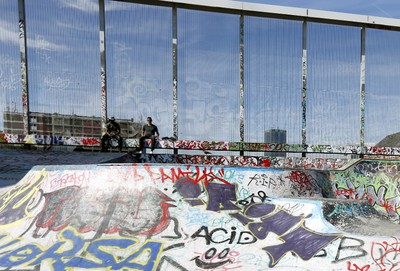 Youths sit at a skateboard park covered with graffiti beside the 12th-century church of Notre Dame de la Chapelle (unseen) on the edge of the Marolles district in Brussels, Belgium, August 5, 2015. Once the last refuge of lepers and criminals, one of Brussels' quirkiest neighbourhoods teems with vintage furniture sellers, flea markets and linguistic invention. Les Marolles in French, or de Marollen in Dutch, stretches from the Gare du Midi, where Eurostar trains arrive, to the city's highest point, the Mont des Pendus or Galgenberg (Gallows Hill), where you can look down on half of Brussels. Picture taken on August 5, 2015. REUTERS/Francois Lenoir