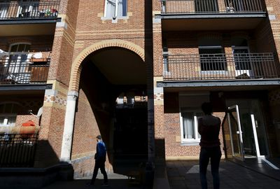 Residents are pictured in the Cite Hellemans, an early 20th-century project by architect Emile Hellemans, who sought to replace unhygienic alleyways and cramped homes with planned, aesthetic social housing in the Marolles district in Brussels, Belgium, August 5, 2015. Once the last refuge of lepers and criminals, one of Brussels' quirkiest neighbourhoods teems with vintage furniture sellers, flea markets and linguistic invention. Les Marolles in French, or de Marollen in Dutch, stretches from the Gare du Midi, where Eurostar trains arrive, to the city's highest point, the Mont des Pendus or Galgenberg (Gallows Hill), where you can look down on half of Brussels. Picture taken on August 5, 2015.  REUTERS/Francois Lenoir