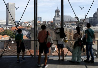 Tourists watch the cityscape from the Marolles elevator, an urban elevator connecting the lower and higher levels of the Brussels' district, Belgium, August 5, 2015. Once the last refuge of lepers and criminals, one of Brussels' quirkiest neighbourhoods teems with vintage furniture sellers, flea markets and linguistic invention. Les Marolles in French, or de Marollen in Dutch, stretches from the Gare du Midi, where Eurostar trains arrive, to the city's highest point, the Mont des Pendus or Galgenberg (Gallows Hill), where you can look down on half of Brussels. Picture taken on August 5, 2015. REUTERS/Francois Lenoir