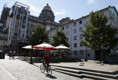 A cyclist climbs a street towards the Brussels' Palace of Justice (back C) and the Marolles elevator (L), an urban elevator connecting the lower and higher levels of the district, August 3, 2015. Once the last refuge of lepers and criminals, one of Brussels' quirkiest neighbourhoods teems with vintage furniture sellers, flea markets and linguistic invention. Les Marolles in French, or de Marollen in Dutch, stretches from the Gare du Midi, where Eurostar trains arrive, to the city's highest point, the Mont des Pendus or Galgenberg (Gallows Hill), where you can look down on half of Brussels. Picture taken August 3, 2015. REUTERS/Francois Lenoir