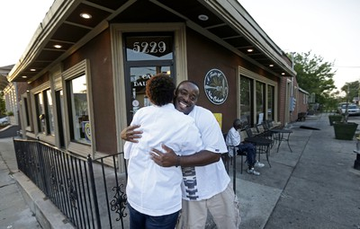 Corey Hinton, right, hugs his close friend Keisha Henry, owner of Cafe Dauphine, outside the restaurant in the Lower Ninth Ward in New Orleans, Tuesday, Aug. 25, 2015. For now, the post-Katrina restaurant boom has only one outpost in the Lower 9th Ward, one of the city�s hardest-hit neighborhoods. Longtime resident Keisha Henry opened Cafe Dauphine with relatives, marking a rare sit-down restaurant in an area that traditionally has had only corner stores and takeout.  (AP Photo/Gerald Herbert)