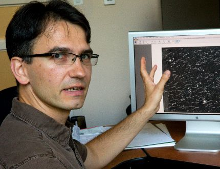 Stanimir Metchev of the Physics and Astronomy department at Western University points out a photograph showing the path and speed of 215 asteroids they found with a new technique, only 59 of these asteroids were previously known. Photographed in London, Ont. on Friday August 28, 2015. (MIKE HENSEN, The London Free Press)