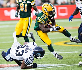 Edmonton running back Shakir Bell takes to the air after being tackled by Toronto's Vincent Agnew during Friday's game at Commonwealth Stadium. (Codie McLachlan, Edmonton Sun)