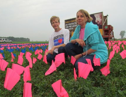 Elizabeth Van Den Assem, left, and Diana Alblas were part of a We Need A Law demonstration that set up 10,000 pink and blue flags along Oil Heritage Line on Saturday August 29, 2015 in Plympton-Wyoming, Ont. Volunteers were expected to be at the display until 6 p.m. Saturday to talk to the public their call for an abortion law in Canada. Paul Morden/Sarnia Observer/Postmedia Network