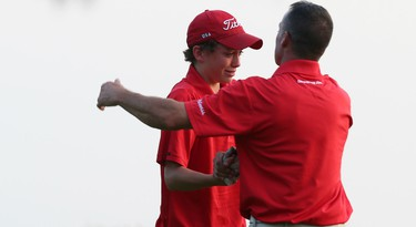 An emotional Hunter McGee, 14, hugs dad and playing partner Allen McGee after capturing the Sun Scramble Flagstick Open Championship with his dad/partner Callen McGee at Eagle Creek Golf Club on Sunday, Aug. 30, 2015. (Chris Hofley/Ottawa Sun)