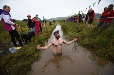 A competitor reacts as he takes part in the 30th World Bog Snorkelling Championships in Waen Rhydd peat bog at Llanwrtyd Wells, south Wales on August 30, 2015. Entrants must negotiate two lengths of a 60-yard trench through the peat bog in the quickest possible time without using any conventional swimming strokes.  AFP PHOTO / OLI SCARFF