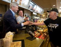 Conservative leader Stephen Harper, left, joined local MP Gord Brown serving coffee to Conservative supporters as he stops at a Tim Hortons in Gananoque on Monday. (CANADIAN PRESS)