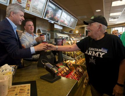Prime Minister Stephen Harper and Leeds-Grenville MP Gord Brown serve coffee to Conservative supporters as Harper made a stop at a Tim Hortons in Gananoque on Monday. (THE CANADIAN PRESS/Adrian Wyld)