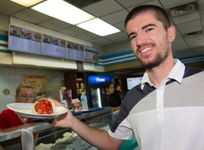 Nick Konjuvca, owner of Uncle Nick?s Souvlaki, holds up a gyro in his First Street eatery in London. Konjuvca took over the former Sammy?s Souvlaki across from Fanshawe College on Oxford Street. (CRAIG GLOVER, The London Free Press)