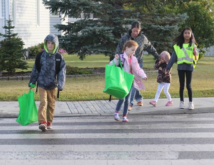 St. Kateri Catholic school students Layton Gordon (left), 10, Summer Gordon, 7, walk across the crosswalk while their mom, Amber Gordon, brings Camden Gordon, 4, behind them, as AMA School Safety patroller, Jullianna Pasia, 11, stops traffic for the hockey players at St. Kateri Catholic school on Mission Heights Drive on Tuesday September 1, 2015 in Grande Prairie, Alta. The Alberta Motor Association (AMA) School Safety patrollers were out helping younger students cross the street on the first day of school. Alexa Huffman/Grande Prairie Daily Herald-Tribune/Postmedia Network