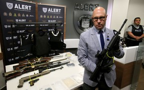 ALERT Insp. Darcy Strang holds one of the assault rifles that was seized along with seven other firearms, three body armour vests were seized and an estimated $125,000 worth of drugs in a joint investigation with Bonnyville RCMP. Tom Braid/Edmonton Sun/Postmedia