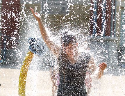 Logan Smith Rodrigues (13) cools off under a cascading sheet of water at the Ivy Park splash pad in London, Ont. on Thursday September 3, 2015. (DEREK RUTTAN, The London Free Press)