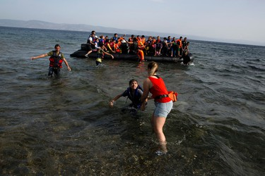 A volunteer helps a Syrian boy as he arrives with others on a dinghy after crossing from Turkey, on the island of Lesbos, Greece, Monday, Sept. 7, 2015. The island of some 100,000 residents has been transformed by the sudden new population of some 20,000 refugees and migrants, mostly from Syria, Iraq and Afghanistan. (AP Photo/Petros Giannakouris)