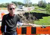Brent Mackie stands by a large sinkhole open on Ness Avenue at Sturgeon Creek on Monday Sept. 07, 2015. The sinkhole opened during heavy rains last Friday.