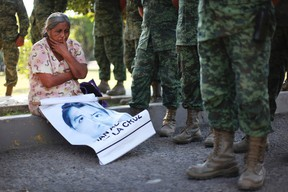 In this Dec. 18, 2014 file photo, the mother of missing college student Adan Abarajan de la Cruz sits at the foot of soldiers outside a military base during a protest by the families of 43 missing students. A group of independent experts said Monday, Aug. 17, 2015, that Mexican authorities withheld information from family members of students who disappeared after a confrontation with police. (AP Photo/Felix Marquez, File)