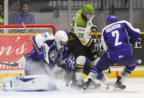 Sudbury Wolves goalie prospect Matthew Menna looks for the puck between the legs of teammate Trenton Bourque (2) as North Bay Battalion's Mathew Santos attempts to score during the first period of OHL pre-season play at Memorial Gardens this past September. Postmedia Network file photo