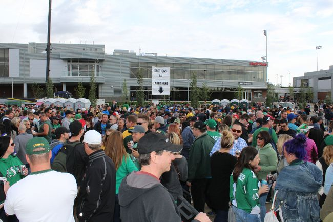 Fans of the Edmonton Eskimos and Saskatchewan Roughriders wait to enter Shell Place for the Northern Kickoff match in Fort McMurray, Alberta on June 13, 2015. VINCENT MCDERMOTT/POSTMEDIA NEWS/TODAY STAFF