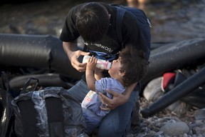 An Afghan refugee feeds a baby milk moments after arriving on the Greek island of Lesbos, September 9, 2015. Greece asked the European Union for aid to prevent it being overwhelmed by refugees, as a minister said arrivals on Lesbos had swollen to three times as many as the island could handle. (REUTERS/Dimitris Michalakis)