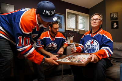 Long time fan and season ticket holder Bob Kindrachuk (right) shows Edmonton Oilers Cam Talbot (centre) and Nail Yakupov (left) his Oilers Stanley Cup memorabilia after the NHL players dropped off his season tickets at his home in Edmonton, Alta., on Wednesday September 9, 2015. Kindrachuk and his friends have atttended Oilers games since the team's start in Edmonton in the late 1970's. Ian Kucerak/Edmonton Sun/Postmedia Network