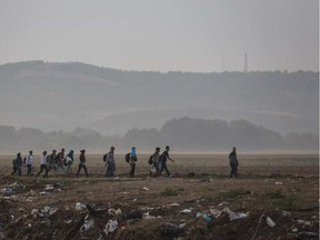 Syrian refugees walk through a field near the border town of Idomeni in northern Greece to cross into Macedonia in this file photo from early in 2015. SANTI PALACIOS / AP