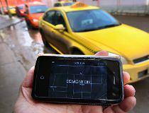 Phone app with Uber website in front of a line up of taxis at the downtown bus station in Edmonton.