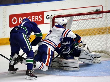 Edmonton Oilers' Connor Rankin gets hit by Evan McEneny in front of Vancouver Canucks' goaltender Clay Witt during Young Stars game at  Penticton, BC on September11 2015. Perry Mah/Edmonton Sun/Postmedia Network