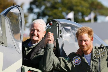 Prince Harry poses for a photograph with veteran Tom Neill after he flew in a Spitfire during a Battle of Britain display at Goodwood Aerodrome in West Sussex, England, September 15, 2015. Prince Harry gave up his seat for Tom Neill after the aircraft he was due to fly in developed a fault. Battle of Britain veterans and wounded servicemen supported by Prince Harry's Endeavour Fund took part in a flypast to mark the 75th Anniversary of victory in the Battle of Britain. REUTERS/Kirsty Wigglesworth/Pool