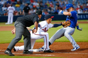 Cliff Pennington of the Toronto Blue Jays is safe at first base under the tag of Daniel Castro of the Atlanta Braves after hitting a RBI single at Turner Field in Atlanta on Sept. 15, 2015. (Kevin C. Cox/Getty Images/AFP)