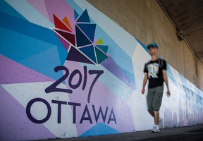 A man walks past a large mural on the walls of the Metcalfe Street/Queensway overpass promoting the events taking place in Ottawa to celebrate the 150th anniversary of Canada. Wednesday September 16, 2015. Errol McGihon/Ottawa Sun/Postmedia Network